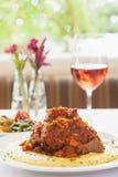 Bräserat kalvkött på säng av polentaen med ett exponeringsglas av vin Royaltyfria Foton