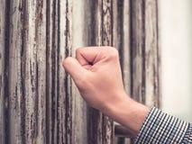 Bräunte Hand eines Mannes in einem karierten Hemd, das seine Faust in der alten und schäbigen Haustür zerstößt lizenzfreie stockfotografie