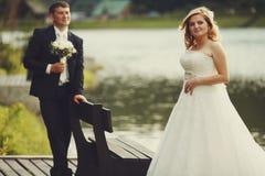 Bräutigam bewundert eine recht blonde Braut, die hinter einem Fluss steht Stockbild