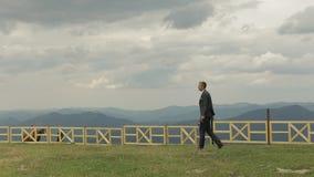 Bräutigam, brunette junger Mann, der auf die Oberseite der Berge geht Langsame Bewegung stock footage