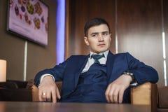 Bräutigam, der auf dem Lederstuhl im Hotel sitzt Stockfoto