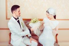 Bräutigam, der bezaubernder Braut Blumenstrauß gibt stockbild