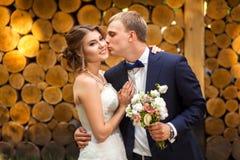 Bräutigam, der Braut nahe hölzernen Klotz küsst stockfotografie