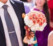 Bräutigam, der einen Blumenstrauß hält Stockfotos