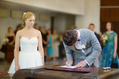 Bräutigam, der einen Hochzeitsvertrag unterzeichnet Stockfotos