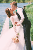 Bräutigam, der glückliche Braut nahe Teich küsst Lizenzfreies Stockfoto