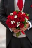 Bräutigam, der ihr rosafarbenen Blumenstrauß zeigt Lizenzfreies Stockbild