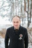 Bräutigam, der im Winterwald steht Stockbild