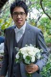 Bräutigam, der schöne Weißrose hält Stockbilder