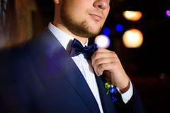 Bräutigam, der seine Fliege mit seinen Händen hält Lizenzfreie Stockbilder