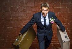 Bräutigam in einer Klage und in zwei Kofferläufen weg Lizenzfreie Stockfotografie