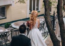 Bräutigam geht blonde nahe mit der Eisenbahn befördernde Rückseite der Braut Stockfotos