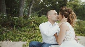 Bräutigam gibt der Braut auf dem Hintergrund der Natur einen leichten Kuss stock footage