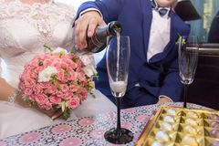 Bräutigam gießt Champagner in Gläser stockbilder