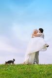 Bräutigam hält Braut in seinen Armen an Stockbilder