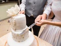Bräutigam hält Brauthand, um einen Kuchen zu schneiden Stockfotos