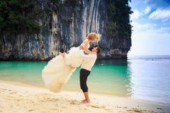 Bräutigam hebt blonde gelockte Braut im flaumigen Kleid auf Strand an Stockfoto