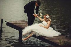 Bräutigam hilft einer hübschen Braut, auf der alten Holzbrücke oben zu stehen Lizenzfreies Stockfoto