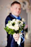 Bräutigam-Holding-Hochzeitsblumenstrauß von Blumen Stockbild