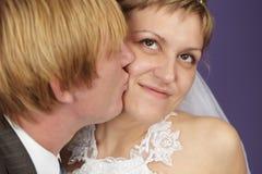 Bräutigam küßt Braut stockfotografie