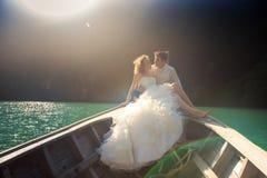 Bräutigam küsst blonde Braut in flaumigem auf Nase von longtail Boot Lizenzfreie Stockbilder