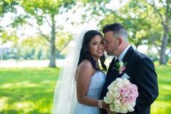 Bräutigam küsst Braut auf ihren Backen, kaukasischen Bräutigam und asiatischen Braut stockbild