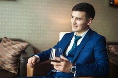 Bräutigam mit dem Glas Whisky sitzend auf dem Stuhl Lizenzfreies Stockfoto
