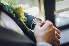 Bräutigam mit einem Boutonniere und einer Uhr Bräutigam waching auf der Uhr Schöne Hochzeit stockfoto