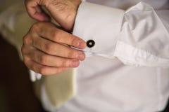 Bräutigam morgens, der Stulpen auf seiner Klage knöpft Lizenzfreie Stockfotos