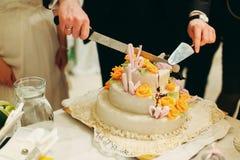 Bräutigam schneidet eine geschmackvolle Hochzeitstorte Stockfotografie