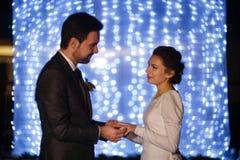 Bräutigam setzt Hochzeitsband auf bride& x27; s-Finger Stockfotos
