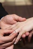 Bräutigam setzt Ring auf Braut Stockbild