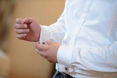 Bräutigam setzt sich auf den Manschettenknopf Stockfotos