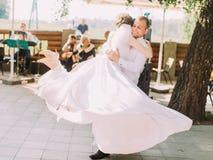 Bräutigam spinnt die reizende Braut im langen Hochzeitskleid stockfotos