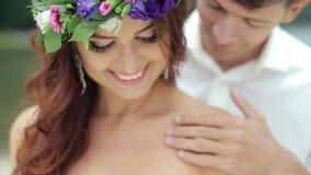 Bräutigam Stroking ein überreichung die Schultern der Braut gab das Lächeln, das unten schaut stock video footage