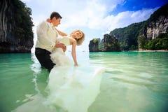 Bräutigam umarmt blonde Braut in flaumigem im flachen azurblauen Meer Lizenzfreie Stockfotos
