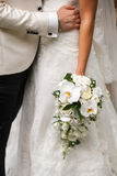 Bräutigam umarmt Braut, die einen Blumenstrauß hält Lizenzfreies Stockbild