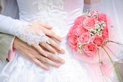 Bräutigam umfasst die Braut, die Brautgriffe ein Hochzeitsblumenstrauß Lizenzfreies Stockbild