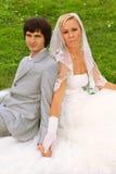 Bräutigam und Braut, die auf grünem Gras sitzen Lizenzfreies Stockfoto
