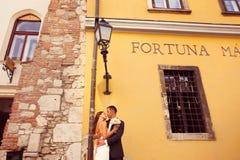 Bräutigam und Braut, die in der Stadt aufwerfen Stockfotografie