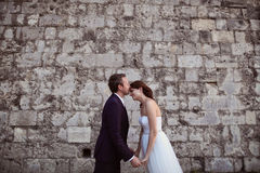 Bräutigam und Braut, die nahe Backsteinmauer küssen Stockbilder