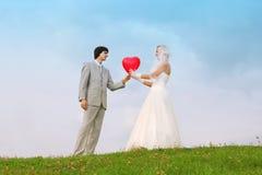 Bräutigam und Braut halten heart-shaped Ballon stockfoto