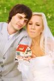 Bräutigam und Braut halten kleines Haus auf Händen Lizenzfreies Stockbild