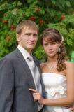 Bräutigam und Braut im weißen Kleid auf Hintergrund von grünen Bäumen Stockfotos