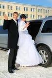 Bräutigam und Braut stehen nahe Hochzeitslimousine Lizenzfreie Stockfotos
