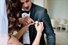 Bräutigam und Braut tragen einen Boutonniere zuhause Lizenzfreies Stockbild