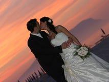 Bräutigam- und Brautsonnenuntergangküssen Stockfotos