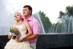 Bräutigam und die Braut gegen einen Brunnen. Lizenzfreie Stockfotografie