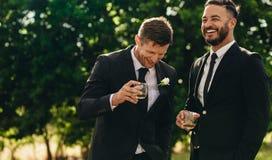 Bräutigam und Trauzeuge, die am Hochzeitsfest trinken stockfoto