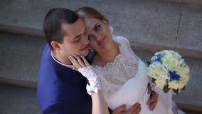 Bräutigam untersucht die Kamera während der Bräutigam, der leicht seine Backe streicht stock footage